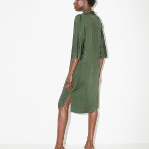 Denne kjole har forlænget søm, korte ærmer og en blød tekstur, som gør den velegnet til enhver anledning. Kjolen har nogle pletter bagpå, som fremgår af billedet. Det ses dog kun, hvis man leder efter det. Materiale: 94% viskose, 6% elastan. Mål str. XXS: bryst 50cm, længde 96cm og ærmelængde 51cm.  Nypris: 1700kr.   #30dayssellout.