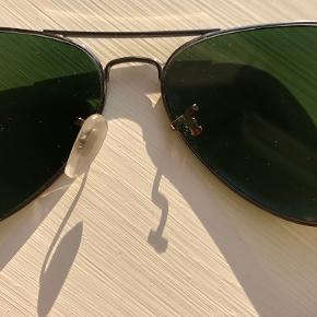 Ray Ban Aviator str L (58) i mørkt sølvstel og grønt glas. De har nogle år på bagen, men er ikke brugt særlig meget. Skal have ny næsestøtte i den ene side.