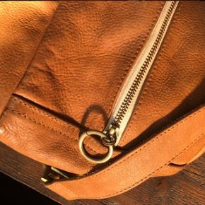 Lækker brun læder taske fra Jocasi butikken i London med fine detaljer på remme. Tasken er af højeste kvalitet og tilmed handcrafted 😍Tasken måler ca. 38 x 27 cm.