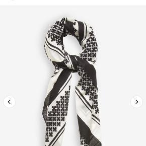 Lækkert let uld tørklæde. Tørklædet er rektangulært. Klassisk Malene Birger signature flower motiv.  Der er et hul i tørklædet, derfor den forholdsvis billige pris.