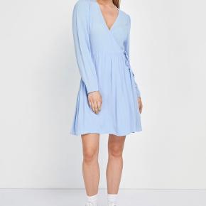 Ensalvation ls dress i serenity fra Envii. Kort lyseblå slå-om kjole med lange ærmer og i 100% viskose. Kjolen er lille i størrelsen.  Jeg sender med DAO og køber betaler fragt.  Jeg bytter ikke.