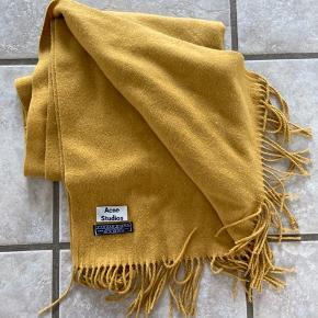 Fejlfrit og blødt Acne tørklæde i karrygul. 100% Virgin Wool.