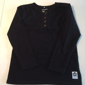 Blød og lækker unisex basis bluse fra Mini Rodini med fine guld trykknapper ved halsen og deres velkendte panda varemærke nederst på blusen.