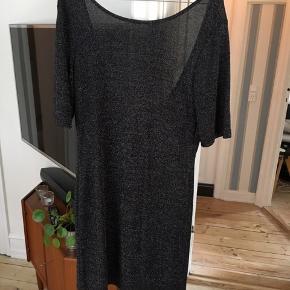 Sort/sølv kjole med dyb rygudskæring. Der er revet i enkelte tråde, men ikke noget man lægger mærke til
