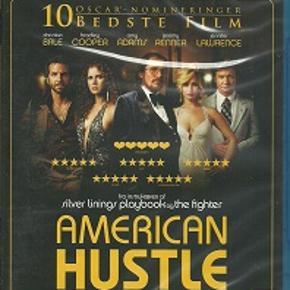 """8805 - American Hustle (Blu-ray)  Dansk Tekst - I FOLIE   American Hustle  Da småfuskeren Irving Rosenfeld (Christian Bale) støder ind i den smukke Sydney (Amy Adams), på trods af, at han allerede sidder i kloen hos sin unge, krævende kone Rosalyn (Jennifer Lawrence), er det kærlighed ved første blik. Irvings problemer er dog først lige begyndt. Helt slemt bliver det, da han og Sydney falder i en fælde sat af FBI agenten Richie DiMaso (Bradley Cooper). Richie smider dem dog ikke i fængsel, i stedet overtaler han dem til at bruge deres evner til at hjælpe ham med at fange endnu større fisk.   Instruktøren David O. Russell er endeligt kravlet så langt ud af sin egen mås, at han kan begynde at lave rigtige film. Det har i de sidste par år givet os The Fighter (Oscar til Christian Bale og Melissa Leo) og Silver Linings Playbook (der scorede Jennifer Lawrence en gylden statuette), og nu får vi så American Hustle , der bedst kan beskrives som en Goodfellas -lignende con film / kærlighedshistorie.       Det ER lidt af en kliche at sige det, men det er den nemmeste måde at bekrive American Hustle .... Den er Goodfellas -agtig. Den har en lækker, elegant, jazzet visuel stil, duellerende voice-overs fra de to hovedroller, samt masser af periode musik og periode tøj. Bare scenen, hvor Cooper og Adams, i deres stiveste 70'er puds, ankommer til festen i slow-motion, til tonerne af Elton Johns """"Goodbye Yellow Brick Road"""", giver et sug i maven. Men i modsætning til The Wolf of Wall Street , hvor det ofte bare føles som om Scorsese har lavet en dårlig kopi af sig selv, så virker American Hustle frisk og levende! Måske fordi den rent faktisk har et hjerte og en sjæl.   I filmens centrum finder vi trekløveret Bale, Adams og Cooper, og lidt ude på sidelinien - reelt 20 år for ung til sin rolle - har vi Lawrence. De fire hovedroller giver den hele armen! Lawrence har stjålet alt opmærksomheden, ikke overraskende, for hun får lov til at give en larmende, opmærksomhedskrævende præstation"""