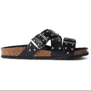 Cool sandaler fra Shoe The Bear.  Helt nye og ligger i org. æske.  Sandalerne har krydsende remme over forfoden og vristen, som er besat  med sølvfarvede nitter. Sandalens sål er lavet af kork med et lag ægte  læder. Snuden er desuden fodformet, og spænderne er justerbare.  Perfekte til sommer sammen med en feminin kjole for en fed kontrast.  Str. 37