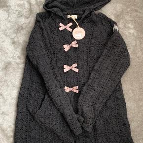 Mørkegrå lækker strik cardigan med sløjfer foran på knapperne som lukker den sammen. Hætte og 2 lommer foran.  Virkelig fin cardigan.