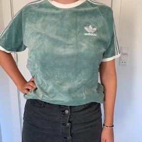 Adidas t-shirt i velour stof  T-shirten er str. s, men er ret lang, længere end på billedet Kan nok også passes af en M