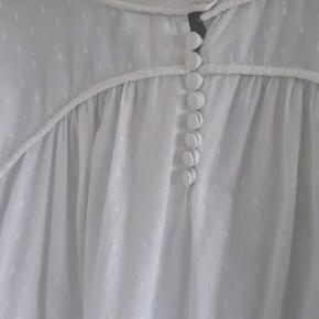 """Smuk hvis skjortebluse i a facon fra         S´NOB Skjorten falder rigtigt pænt, og har små hvide """"bomber"""" broderet i stoffet. Rund hals og stolpelukning med stofovertrukne knapper. 100% bomuld. En knap mangler nederst på venstre ærme."""