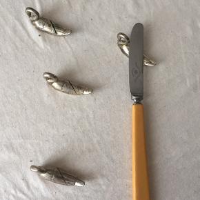 4 stk. Smørkniv holdere formet som svaner fra 70erne  Patinering forekommer  Mål: 5,5 x 1,5 cm