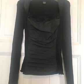 Fin sort bluse fra Oscalito i 70% Lama (uld) og 30% esta (silke). I den bedste ende af godt men brugt uden huller, pletter, fnuller eller lign. Farven er stadig helt sort.  Mål Brystmål: 40 cm på tærsk+ meget strech., dvs 80 cm i omkreds + meget strech. Længde: 66 cm fra nakken og ned. Søgeord: sort bluse langærmet silke silkebluse uldbluse silketop undertrøje wool silk Black ribstrik rib blonder blonde lace fest hverdag