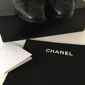 Klassiske ballerinaer fra Chanel i sort lammeskind med snude i sort lak (kalveskind) med CC logo. Købt i Chanel butikken i København (kvittering medfølger).  Str 38.  De er i fin stand - dog skal det bemærkes at den venstre sko har haft en mindre ridse i skindet på indersiden (se billede 6), hvilket dog er udbedret af skomager. De er ligeledes nyforsålet.  Brugt sparsomt og i rigtig fin stand, da jeg altid opbevarer mine sko i deres æske (som afbildet). Alt på billederne medfølger (æske, 1 dustbag, kvittering samt Chanel silkebånd). Nyprisen for denne model er i dag DKK 5.010 (se billede fra hjemmesiden).  Køber betaler porto og TS gebyr men jeg handler gerne via mobile pay.