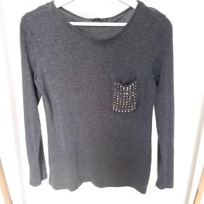 Grey T-shirt with rivets on chest pocket. Light, soft material.