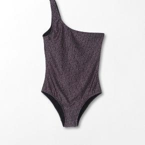 Super fin badedragt fra Becksöndergaard.   - Model Besra med BS mønster - gråligt / rosa print  - med one shoulder - Str. XL, men passer en L-XL - Kun brugt og vasket én gang. Ser ud som ny.  - Troede jeg kunne passe den som gravid, men kan jeg ikke.  - kan også bruges som top til en nederdel, jeans eller shorts  Nypris 599,- men er sat ned til 299,-. Sælges for 150 pp.
