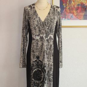 100 % NY: Flot kjole med lange ærmer. Bundfarven er sort. Materialet er 95 % viscose + 5 % elastan.  Oprindelig købspris: 800 kr.  Brystvidde: 65-68 cm x 2 Livvidde: 47-56 cm x 2 Hoftevidde: 57-70 cm x 2 Længde: 100 cm   Ingen byt, og prisen er fast.
