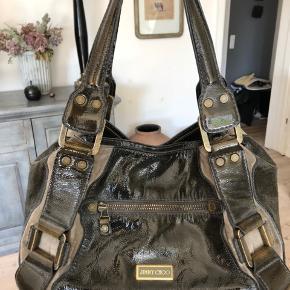 Super lækker anderledes Jimmy Choo taske. Den dyre udgave, da den er med lak og guldspænder. Mega praktisk, da den har rigtig mangler lommer - med lynlåse! Samme model solgt på eBay til 4.500 kr. Har også matchende pung.