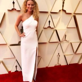 Sælger denne flotte og enkle hvide galla kjole som jeg havde på under dette års Oscar uddeling. Kjolen er helt hvid, men høj slids i den ene side. Der er også en trekantsudskæring i den ene side ved livet, så man viser en smule hud. Stadig klassisk kjole med en strop. Lynlås i siden. Brugt en gang.