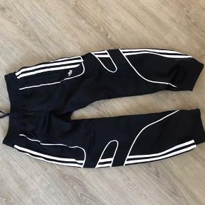 Lækre bukser fra Adidas. Sorte med hvid decor - dog ikke de klassiske hvide striber. Elastik og snøre i livet. Brugte, men fejler intet.