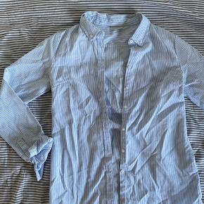 Stribet skjorte i lækkert materiale. Brugt få gange - har mest bare hængt på knagen, desværre. Fejler intet.