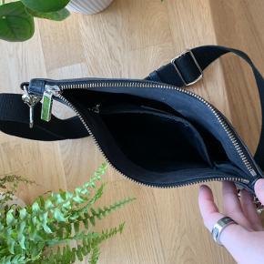 Den har lidt brugskader i metallet på selve lynlåsen, men skindet er i god stand.  Størrelse: 29x19  Tasken i sort skind med anaconda struktur er casual, rå og super anvendelig. Denne tre-i-én taske har en justérbar og aftagelig kanvasstrop, der gør det muligt at bruge den som clutch, skuldertaske samt bæltetaske. Tasken lukkes med lynlås og har en indvendig lomme samt to udvendige, der ligeledes lukkes med lynlås