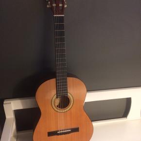 Akustisk guitar med 3-måneder gamle strenge. Guitartaske medfølger.