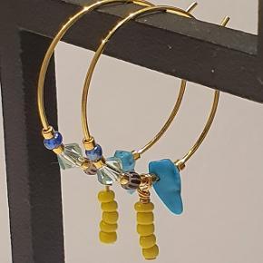 Forgyldte håndlavede kreoler med halvædelsten (flourit, karneol, rosakvarts, turkis, tigerøje, røgkvarts eller ametyst), farvede glasperler og forgyldte perler. Farver/ædelsten varierer afhængig af model (se billede 2). 25 mm i diameter. Nikkelfri.   Sendes via TS med DAO for ca. 32 kr eller uforsikret med postnord til 10.  PRISEN ER FAST.