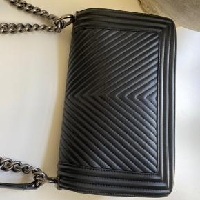 CHANEL OLD MEDIUM BOY CHEVRON BLACK, CALFSKIN WITH RUTHENIUM HARDWARE.  This stunning bag is still in well condition, holds the original shape and the hardware is still very clean and shiny, no visible signs of wear.  Additional information Exterior condition: Used but in a very well condition, corners show no visible signs of damage. Outside of the bag is still clean and only shows minor signs of wear. Inside the bag, used but still very ok.  Includes: Chanel box & authentication card (from Chanel). (Photo attached).