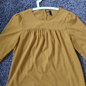 Karrygul ( varm) skjorte med knapper bagpå.  Fin og flot