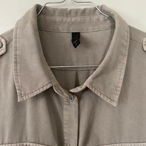 Smart Penelope kjole fra PULZ. Kjolen har krave, bindebånd i taljen og lukkes foran med knapper. Lange ærmer som kan foldes op og fastgøres med en lille knap. Stiklommer foran og brystlommer med klap. Stropper langs skulderne som fastgøres med en knap. Knælang. 76% viskose og 24% polyester. Farve: clay beige.  Aldrig brugt, men mærket er taget af.   Kan sendes på købers regning.