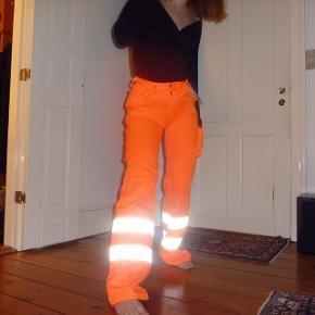 Helt nye ubrugte neon orange refleks bukser fra det lækre mærke Mascot. Tykt, slidstærkt materiale, med en del gode lommer. Oprindelig arbejdsbukser, så de har en rå, edgy vibe. Sidder stramt i taljen og er så cool!  Især her til forår/sommer, hvor neon spås til at blive den helt store trend. Bukserne er desværre købt for små , så har netop selv bestilt et nyt par. De passer en xs eller en s.