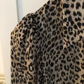 Skjorte i leopard med små skulderpuder.  Den er længere bag på end foran.  Ingen fejl eller mangler.  Bytter ikke.  OBS: Jeg sender kun ved en evt. handel.