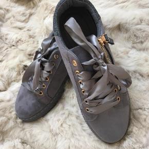 Varetype: Købt hos BUCH Størrelse: 39 (38) Farve: Grå  OBS: Kun handel via KØB NU (læs profil).  Skønne sko med feminine detaljer. Silkesløjfer og pyntelynlåse. Små i str. - jeg bruger normalt 38, men passer disse fint.  Bytter ikke. Prisen er fast.  Porto = DAO