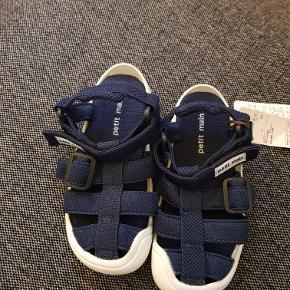 Mærke: Petit main  Helt nye og fine sandaler med justerbar velcrolukning. Mørkeblå med let shimmer i overfladen.  Ubruge og har stadig mærke på.  str. 16cm/26