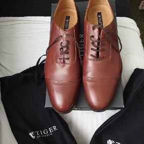Helt ny sko fra Tiger of Sweden, model Lundh, farve 12s/cognac, str 43. Dustbags til  skoene medfølger. Nypris 2500 kr.