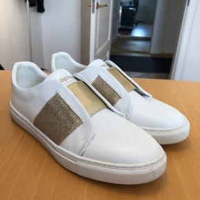 Flotteste sneakers med elastikbånd i guld. Brugt ganske få gange og kun indendørs. Fremstår næsten som ny.
