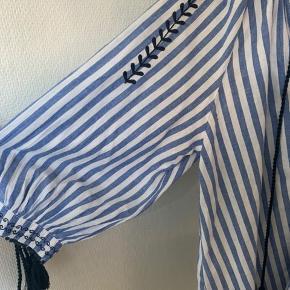 """Let Lyseblå og hvid stribet bluse (skjorte / tunika agtig) i str S. Med mørkeblå bånd og broderi detaljer. Man kan evt klippe bånd af! Oversize model så passes fra XS til M - se mål. Længde bagpå målt midtpå ca 74 cm Ca 5-7 cm kortere foran afhængig hvor man måler. Bredde fra ærmegab til ærmegab ca 61,5-62 cm 3/4 """"pufærmer""""fra armhule og ned ca 29 cm Materiale let tyndt bomuld Hvis afhent 135 #Secondchancesummer"""