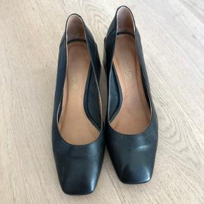 Black leather heels with square toe and square heel. Very Elaine from Seinfeld vibes!! Looks great with jeans.   I don't know the brand, but they are made in Spain. Feel very good quality, and super comfortable.   Worn once, and they have a few small scratches, which aren't very noticable unless you look for them.