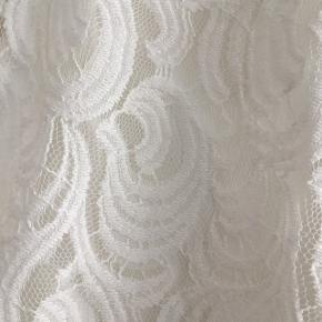 Fin blondebluse i råhvidt blondestof med aftagelig jersey-stroptop indenunder.  Begge lag er elastiske. Sender gerne. Køber betaler porto.