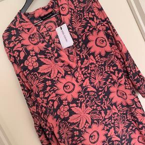 Sissel Edelbo kjole Model: Fleur de Lis kaftan dress kjole  Størrelse: One Size  Købspris: 999,-  Super flot kjole fra Sissel Edelbo Ny og stadigvæk med prismærke Super flot og utrolig lækker  Denne smukke kjole er lavet af genanvendte sarier. Alle sarier er håndplukkede af Sissel Edelbo, og er, før de blev re-designet, blevet båret af en indisk kvinde. Kvindens og sariens historie viser sig i de unikke mønstre og små karakteristika. Ved at bære denne smukke kjole fra Sissel Edelbo fortæller du historien videre.  Sissel Edelbos produkter er lavet af vintage sarier. Da stoffet er genanvendt, kender vi ikke den totale sammensætning af stoffet, som er håndplukket i Indien som en silke-mix. Der kan af samme grund forekomme små fejl i stoffet. De små fejl er en del af sariens charme og historie og betragtes ikke som reklamation.  Alle produkter fra Sissel Edelbo er unikke.  Dvs der kun findes den ene du ser her på billedet og kun i den viste størrelse.  Dét gør din kjole helt unik - og et smukt og farverigt alternativ til andre kjoler.  LET THE STORY CONTINUE - FROM ONE WOMAN TO ANOTHER