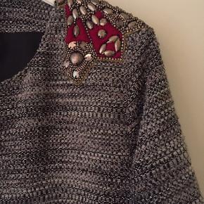 Flot jakke med pynt på begge skuldre, gråmeleret med lidt sølvlurex i stoffet.  Bytter ikke.