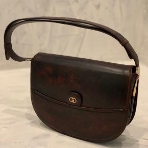 GUCCI • HANDBAG 1780,-  Vintage Gucci taske med det klassiske logo. Tasken er rummelig og har derfor plads til det meste. Den har på bagsiden en baglomme, indvendigt et stort rum samt et mindre med lynlås lukning. Taskens rem kan forlænges så den også kan bruges som crossbody 😍 Der er en mindre skade som vist på billedet, men udover dette fremstår tasken pæn og uden særligt slid. Tasken er i brune nuancer.   H 19 cm D 7 cm B 26,5 cm   Der følger ikke noget med til denne taske.       Flere billeder kan ses i kommentar.