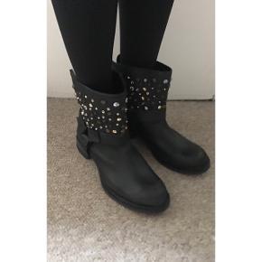 """Sælger disse super fede støvler med nitter fra Zara (Trafaluc-linjen) i ægte læder. Købt i Barcelona.  Aldrig brugt, stadig med mærket på. Støvlerne er lavet med et lidt """"slidt look"""", så læderet er ridset med vilje.  Str. 38, true to size. Sålen måler 27,5 cm nedenunder Skaftet måler 16,50 cm  Hælen måler 3 cm  Kan sendes med DAO via Trendsaleshandel eller mødes og handle i København K :)"""