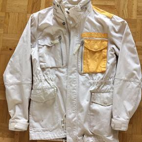 Næsten ikke brugt. Har nogle pletter (se billede 2 og 3) på den ene lomme og bag på den ene skulder - pletterne er ikke forsøgt fjernet. Pga pletterne sælges jakken mega-billigt.