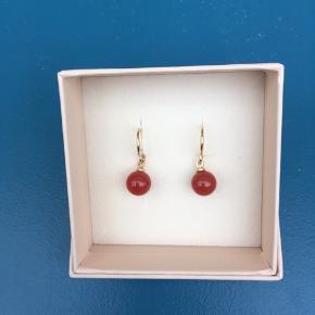 Fine og ubrugte forgyldte øreringe med rødlig sten, har fået dem i gave men kan ikke lide at gå med øreringe. Giv et bud!