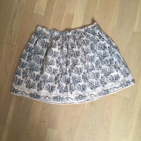 Den fineste nederdel med blomster, lommer i siderne og lynlås venstre side. Sælger fordi den desværre er købt lidt lille.