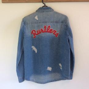 Super fin demin jakke/skjorte fra Sofie Schnoor. Jakken har et råt forvokset look med slid flere steder og Rustlers print på ryggen. Kan bruges både inde eller som jakke forår/sommer.