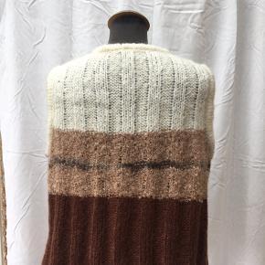 Lækker, varm vest fra Kello.  Materialet  er mohair  og uld - vesten kan maskinvaskes på uldprogram.  Længde: 56 cm Bryst: 2x55 cm, men kan strækkes.  Farverne er råhvid, lys brun og mørkebrun med en enkelt stribe sort.  En superlækker vest til efterår og vinter 🍁🍂