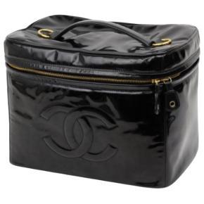 Chanel kosmetik taske i sort lak materiale. Den er brugt med alm. Brugerspor. Men virkelig smuk stadig og fin!   Måler 19x21 cm  Kvittering følger med