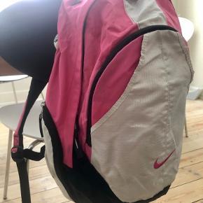 Fin pink rygsæk / skoletaske fra Nike med masser af lommer, så indholdet er let at finde.   Jeg kan sende flere billeder. Der er lidt pletter foran på det grå, som jeg har prøvet at få med på et foto, som jeg kan sende.  Men tasken er stadig fin og kan forestille mig, at det kan fjernes med en klud el lign.   Sender gerne eller kan afhentes i Valby (lige ved Valby station).  Se også mine andre annoncer :)