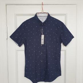 Kortærmet skjorte fra Level Ten, købt i Brooklyn som gave. Desværre i forkert størrelse og derfor aldrig brugt. Har stadig prismærker på.  Sælges billigt pga. en enkelt lille ujævnhed i materialet (se detaljebillede).